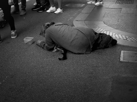 beggar lying on the ground to give alms Photo