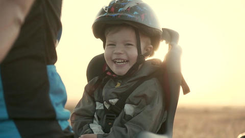 A boy of 2-3 years old in a helmet and in a children's bicycle seat. Dawn Footage