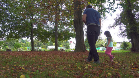 Father walking walking with daughter in park in autumn foliage Live Action