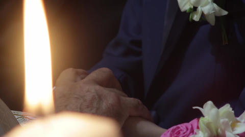 Priest holding the clasped hands of the bride and groom to light a candles held  Footage
