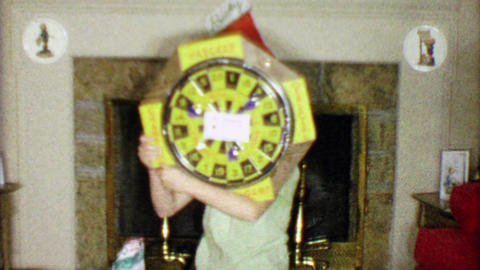 1963: Boy gets dartboard for Christmas gift in front of holiday fireplace Footage