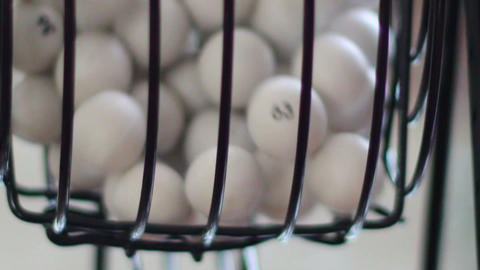 White bingo balls rolling inside a bingo cage Footage