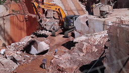 workers working in marble stone quarry with backhoe loader, slider shot Footage