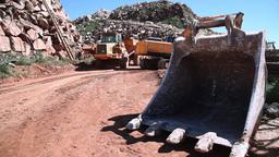 excavator filling dump truck with excavator bucket on the floor, slider shot Footage