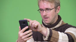 Studio shot of happy handsome man using phone and looking surprised Footage