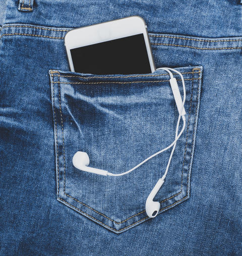 smartphone with headphones in the back pocket of blue jeans Photo