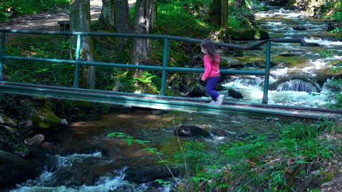 Little girl crossing dangerous bridge over a Mountain river - stream flowing Footage