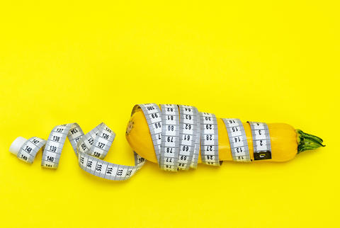 yellow zucchini wrapped in a measuring tape Photo