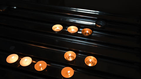 Red candles stand in the Catholic church. Candles symbol of grief and mourning Footage