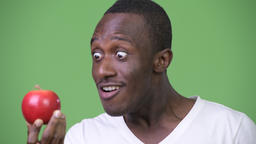 Young happy African man looking at red apple Footage