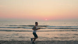 Sporty Man is Jogging on Beach and Running along Ocean Coast at Sunset Footage
