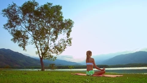 woman relaxes in pose Lotus by tree against hills backside Footage