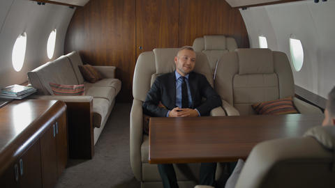 Private jet cabin with businessman in armchair. He have conversation with Footage