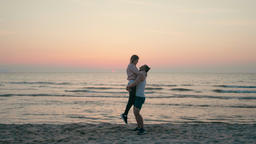 Young Happy Couple is Swirling from Happiness on Sea Beach at Sunset in Summer Footage