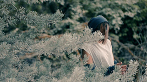 extravagant woman stands in a pine forest and holds pine cones in her hands Footage
