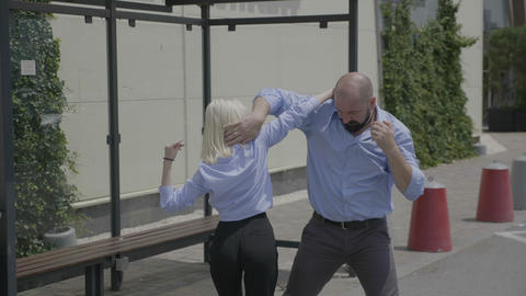 Happy couple of bearded strong business man and young cute woman street dancing Footage