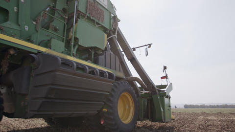Cotton picker harvesting a cotton field creating large cotton bales GIF