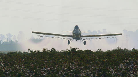 Crop duster spraying chemicals over a cotton field - slow motion GIF