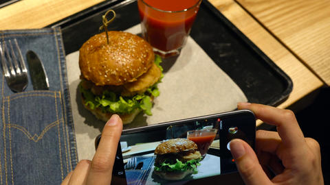 Girl makes a photo of burger and tomato juice on a smartphone in a cafe close up 영상물