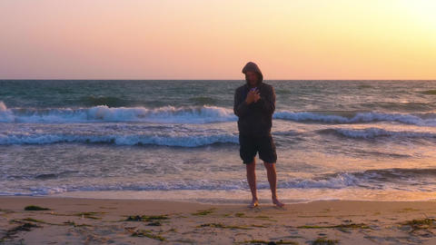 Sportive man warming up hands before stretching on seashore in the morning Live Action