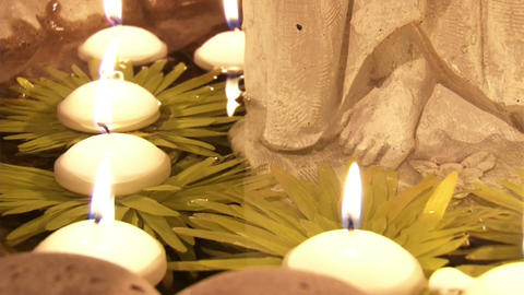Lighted candles slowly float through the water in the temple Stock Video Footage