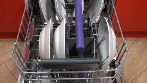 man takes out clean dishes from the dishwasher Footage