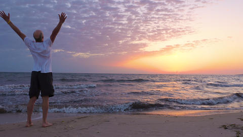 Free tourist rising hands and looking at sunrise on seascape with copy space Footage