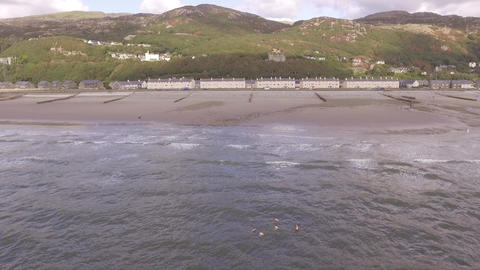 Aerial footage flying towards Barmouth beach from the sea Live Action