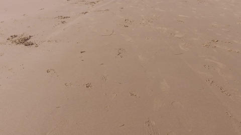 Fast, low aerial footage over Barmouth beach sand Live Action
