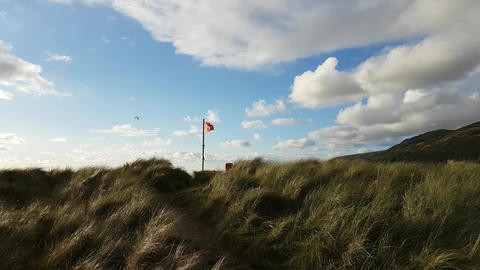 Red flag in the wind, sand dunes, Wales UK Live Action