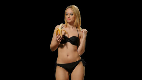 Blond girl in a bathing suit eating a banana (alpha channel) Footage