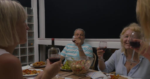 Family clinking glasses at dinner table Live Action