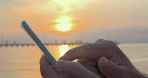 Typing in Smartphone at Sunset Footage