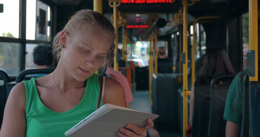 Young woman entertaining with pad during bus ride Footage