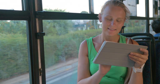 Smiling woman communicating on pad in the bus Footage