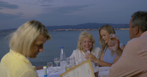 Family spending evening in outdoor cafe at seaside Footage