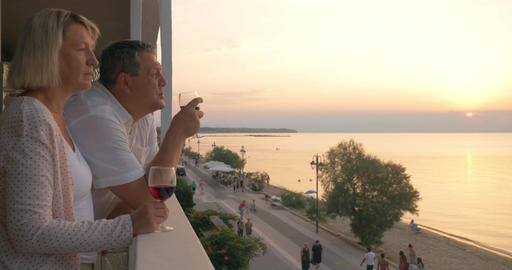 Couple drinking wine and looking at resort from balcony Footage