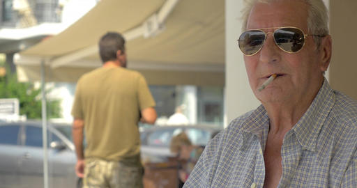Senior man wearing sunglasses smoking in the street Footage