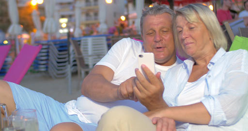 Mature couple using smart phone on the beach Footage