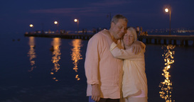 Loving senior couple on water-front at night Footage