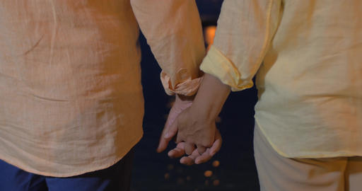 Close-up of man and woman holding hands at sea Footage