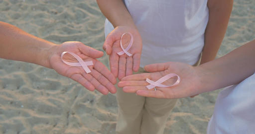 Three Hands Holding Breast Cancer Awareness Ribbon Footage