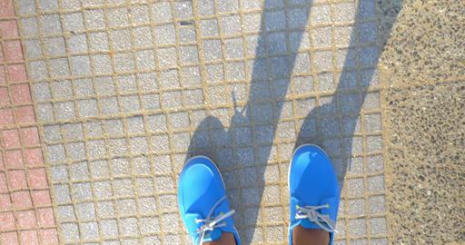 Male feet in blue shoes walking on street Footage