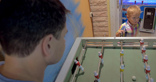 Father and Son Playing Foosball in Arcade Footage