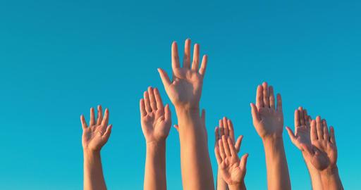 Raised hands against blue sky Footage