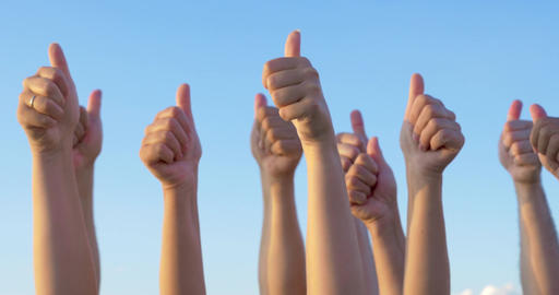 Hands with thumbs up raised against blue sky Footage