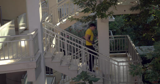 Sportive man walking downstairs in hotel Live Action