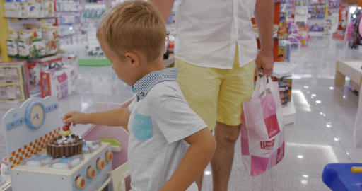 Child is attracted with toy cooker in supermarket Footage