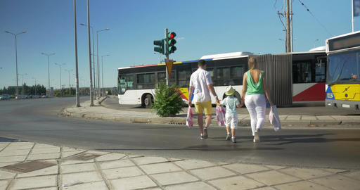 Family with shopping bags crossing the road Footage