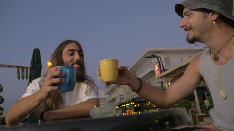 Old friends clanging mugs in outdoor cafe Footage